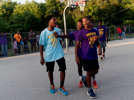 Kyhli Maxey breaks up a heated moment between Da'Breion Ferguson Toombs and an opposing team player during Team GoGo's playoff game at Meaux Park in Milwaukee.