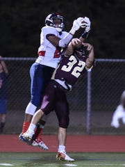 Ketcham's Zaahir Woody makes  a leaping catch against Arlington on Sept. 9.