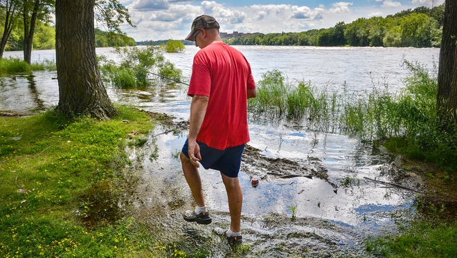 Paul Stiegel, St. Cloud, slogs his way through water that was once shoreline to get to a fishing spot in the Mississippi River Friday, July 15, 2016, at Southside Park in Sauk Rapids. Recent rains have brought the level of the river high enough to flood trees and the park's two fishing piers.