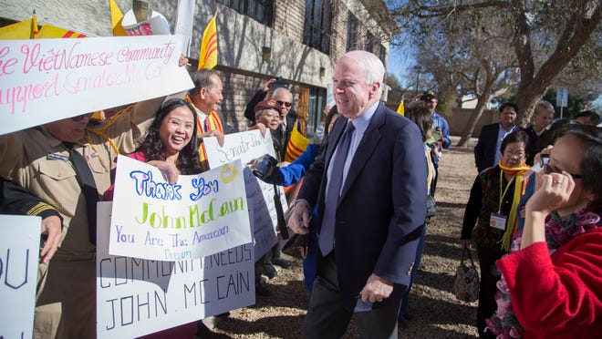 Sen. John McCain is greeted with cheers and signs from Vietnamese outside the AZ State Republican Committee Statutory Meeting at Grace Community Church in Tempe, AZ on January 24, 2015.