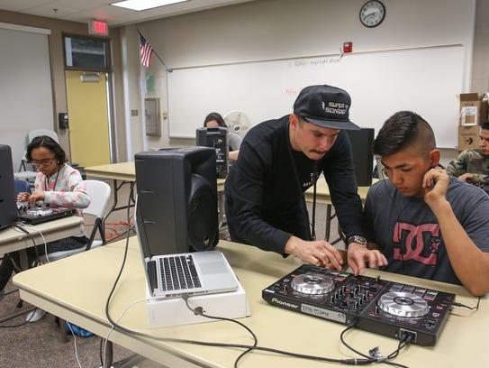 Rafael Lopez (aka DJ Alf Alpha) helps Gerardo Gonzalez