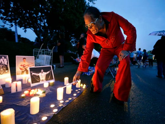 Elvis Whitney, of Denver, Colorado, lights his candle