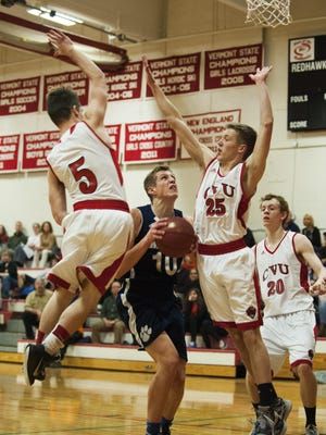 CVU's Jeremy Fuller (5) and Harry Mead (25) guard MMU's Zach Reinhart (10) during the boys basketball game between the Mount Mansfield Cougars and the Champlain Valley Union Redhawks on Thursday night.