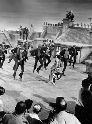 """Actress Julie Andrews dances with the chimney sweeps in the chimney-sweep dance number during filming of """"Mary Poppins"""" on a movie set representing London rooftops at the Disney Studios in Hollywood, Ca., Aug. 16, 1963.  (AP Photo)"""
