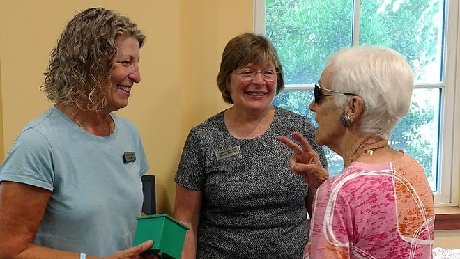 Wendy Thatcher, center, talks with Eileen Smith, left, and a library patron in 2018. Thatcher is retiring after 23 years at the Topsfield Town Library.