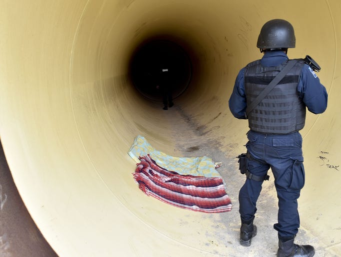 Federal policemen inspect a pipeline under construction