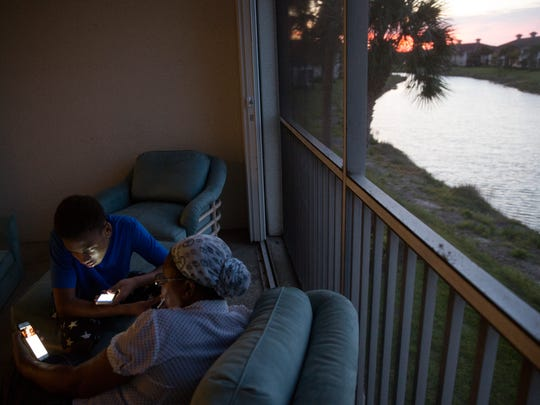 Izaiah Forges, 14, and his grandmother Marie Francois relax on Jude's back porch while searching internet videos at her new apartment at Bridgewater Bay Apartments Thursday, May 11, 2017 in Naples. Jude Forges, along with her sons Izaiah, 14, and Sincere, 7, lost their home Monday, April 10th, 2017 in a fire at Bear Creek Apartments in North Naples.