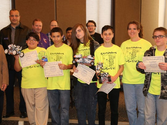 A team From Broadmoor Middle Lab in Shreveport won first place at Northwestern State University's Robotics Competition with robots that competed in challenges related to speed, strength and accuracy. On the front row from left are Dr. Jafar Al Sharab, event coordinator;  Mack Hernandez, Columbus Espree, Cole Cooper, Jose Salguero, Team Sponsor Janet Melancon and Connor Corothers.  On the back row are Dr. Muhammad Benalla, Curtis Deselles, Jason Powell, Dr.Rafiqul Islam and Ross Hennessey.