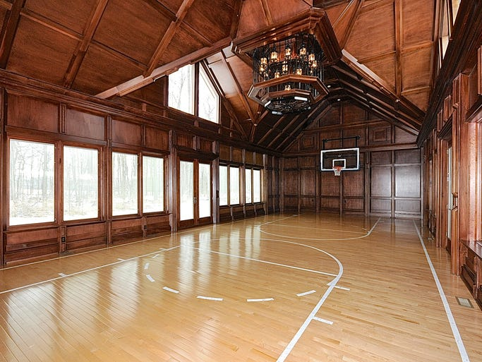 <p>An indoor basketball court doubles as dining space for large dinner parties at this Lizton estate for sale for $3.9 million. The windows are made of sturdy hurricane glass.</p>