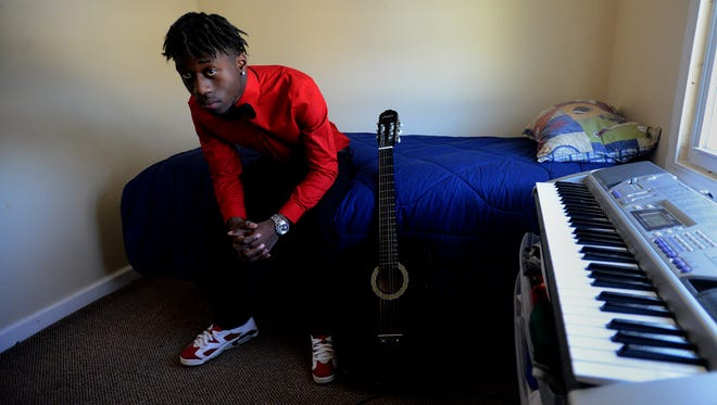 Monntel West, 18, sits on a bed in a room at his aunt's house in Lansing next to a guitar and a keyboard. He's a self-taught pianist who has become an Internet star.