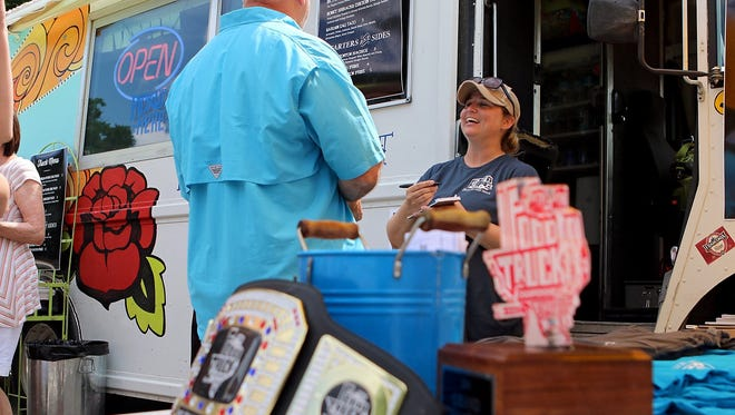 Tagan Couch, owner of the Gypsy Kit, right, takes an order from a customer. The truck was named the Grand Champion of the Food Truck Championship of Texas in 2015.