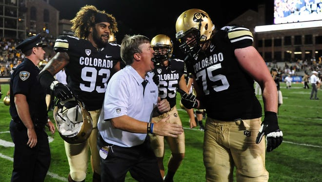 Colorado Buffaloes head coach Mike Macintyre reacts with defensive lineman Samson Kafovalu (93) and long snapper Keegan LaMar (65) and offensive linesman Jack Harris (75)  following the win over the Central Arkansas Bears at Folsom Field.