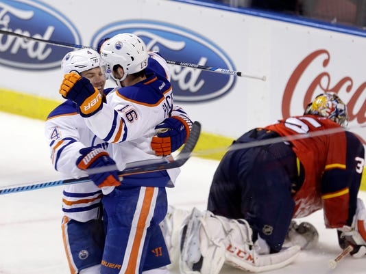 Edmonton Oilers left wing Taylor Hall (4) congratulates teammate Teddy Purcell (16) after Purcell scored against the Florida Panthers during the third period of an NHL hockey game, Monday, Jan. 18, 2016, in Sunrise, Fla. The Oilers won 4-2. (AP Photo/Alan Diaz)