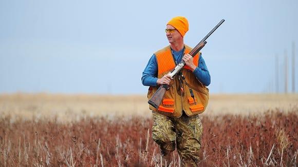 Brett Lovrien of Sioux Falls walks through a field while pheasant hunting near Mitchell.