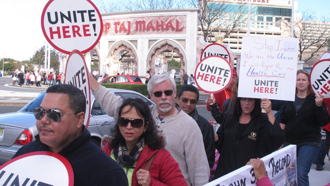 This Oct. 24, 2014 photo shows casino workers picketing the Trump Taj Mahal Casino in Atlantic City, N.J, a week after a bankruptcy judge terminated unionized workers' health insurance and pension benefits. A survey released Monday June 6, 2016 by Local 54 of the Unite-HERE union shows 33 percent of Taj Mahal casino workers have no health coverage at all, while another 50 percent rely on coverage under the taxpayer-subsidized Affordable Care Act.