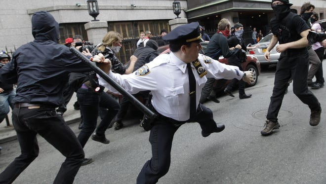 In this May 1, 2012, file photo, a police lieutenant swings his baton at Occupy Wall Street activists in New York. This photo is among the many put on Twitter in response to a New York Police Department request for Twitter users to share pictures of themselves posing with police officers. (AP Photo/Mary Altaffer, File)