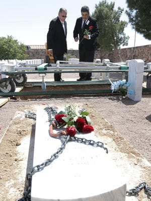 Ray and Daniel Portugal each drop a single rose into their parents' gravesite as their father—World War II veteran Albert A. Portugal—was laid to rest Wednesday at the Fort Bliss National Cemetery.