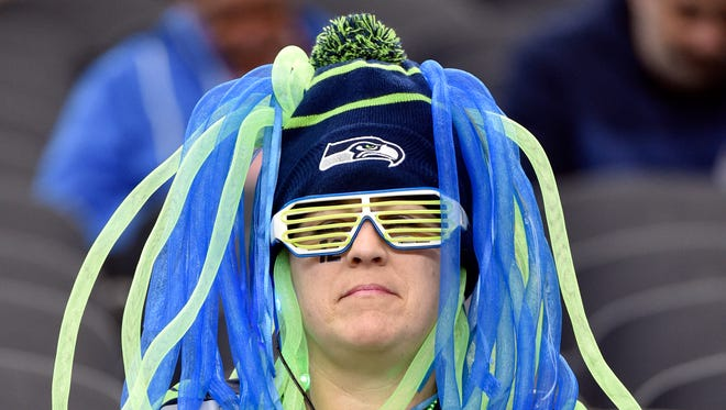 A Seattle Seahawks fan watches the team warm up before an NFL football game against the Dallas Cowboys Tuesday, Dec. 31, 2013, in Arlington, Texas.