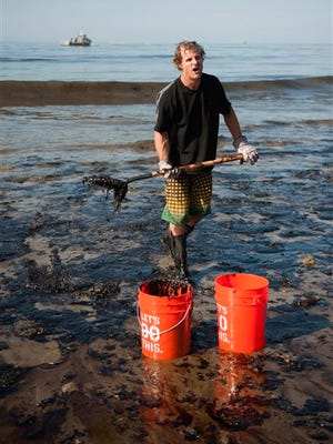 A man shovels up oil on a section of beach about a mile east of Refugio State Beach, Calif., Wednesday, May 20, 2015. A broken onshore pipeline spewed oil down a storm drain and into the ocean for several hours Tuesday before it was shut off. (Kenneth Song/The News-Press via AP) MANDATORY CREDIT; SANTA MARIA TIMES OUT