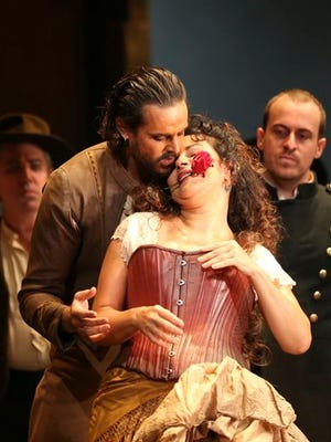 """Nancy Fabiola Herrera, front, playing Carmen, performs on stage during the final dress rehearsal of """"Carmen"""" at the Opera House in Sydney, Australia. An Australian opera company is being criticized for banning as part of a sponsorship deal performances of """"Carmen"""" for two years because the 140-year-old French opera depicts smoking. West Australian Opera had been considering a 2015 staging of the popular opera about a Spanish gypsy named Carmen who works in a cigar factory. The ban lasts the duration of a 400,000 Australian dollar ($355,000) sponsorship deal with a state government health promotion agency, Healthway. The deal begins in March and was revealed in the media on Wednesday."""