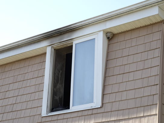 Smoke damage near a second-floor window where a 43-year-old