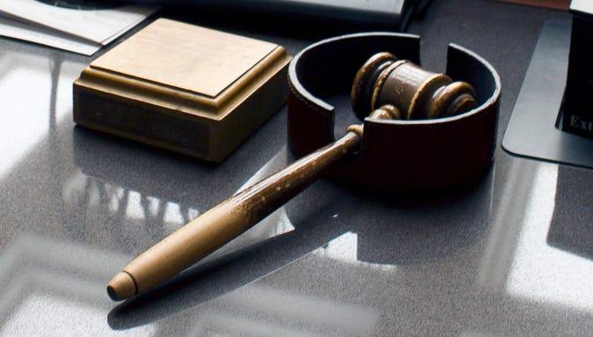 A gavel sits on a desk inside a courtroom.