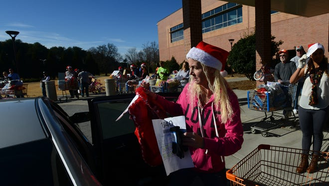 Volunteer Karolyn Ealy helped load presents into a car outside of the TD Convention Center during the annual Salvation Army Christmas Toy Distribution last year. The agency expects to provide Christmas toys and gifts to thousands of children again this year.