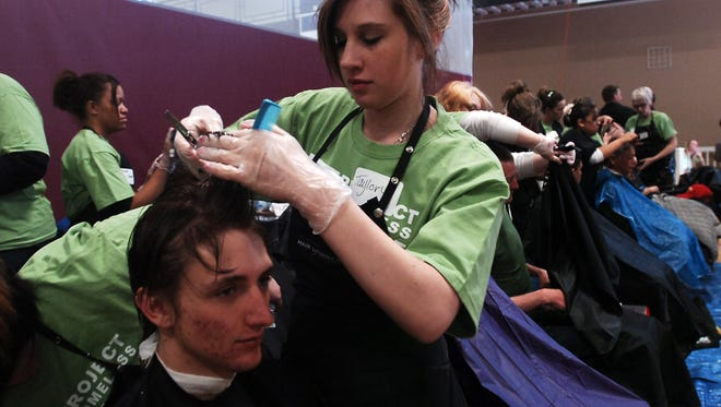 Taylor Rice, a student at Hair Dynamics, in Fort Collins, cuts the hair of Donald Lyberger in this 2011 file photo.