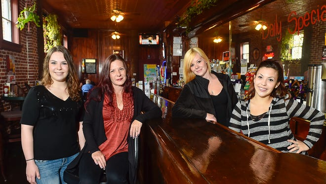Heather Williams (center) poses for a portrait with her daughters in her bar and restaurant Courtyard Grub and Pub in this file photo.