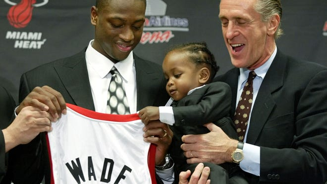 Dwyane Wade gets a little help holding up his jersey from his son Zaire, as Miami Heat coach Pat Riley, right, holds him during a news conference introducing Wade in Miami. In a decision that essentially started what will become a massive shake-up of the franchise, Wade decided Wednesday night, July 6, 2016, that he will leave the Heat after 13 seasons. He agreed to terms on a two-year contract with the Chicago Bulls and will earn about $47 million, instantly making him the highest-paid player on his new team, a distinction he never had in Miami.