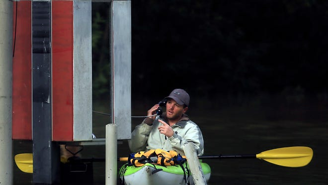 With Russian River waters rising, Dustin Coupe talks with an operator, on River Road in Guerneville on Wednesday.