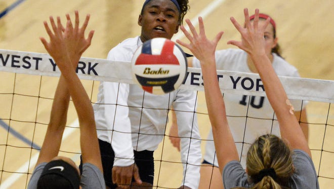 Tesia Thomas of West York crushes the ball past York Suburban blockers Elise Mears, left, and Lulu Mooney, Thursday, Sept. 21, 2017. Thomas' ability to expand her all-around game as a sophomore this year earned her the Y-A League Division II Player of the Year. John A. Pavoncello photo