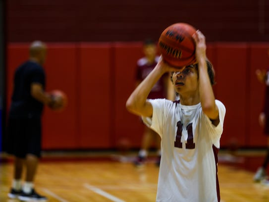 Isaiah Stewart lines up a shot during a drill in First Baptist Academy boys basketball practice on Monday.