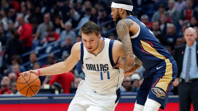 Dallas Mavericks forward Luka Doncic (77) drives against New Orleans Pelicans forward Brandon Ingram in the first half of an NBA basketball game in New Orleans, Friday, Oct. 25, 2019. (AP Photo/Gerald Herbert)