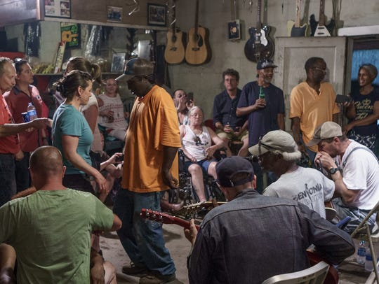 People dance as musicians (bottom right) play blues