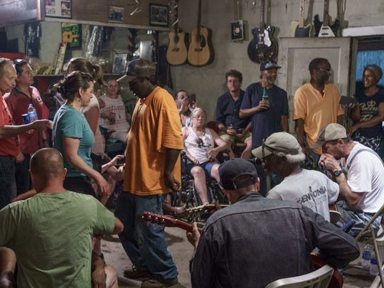 """People dance as musicians (bottom right) play blues at the Blue Front Cafe on June 15, 2018, during the yearly Bentonia Blues Festival. Musicians included (from left) Mike Munson, Blue Front owner Jimmy """"Duck"""" Holmes and Dave Hundreiser."""