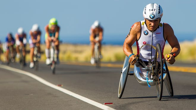Paralympic handcycle gold medalist and two-time CART champion Alex Zanardi leads a pack of racers during the 112-mile cycling portion at the 2014 Ironman World Championship in Kailua Kona, Hawaii.