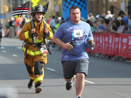 Archive: Justin Montagno, Churchville, dressed in his entire Churchville firefighter gear, finishing a half marathon.