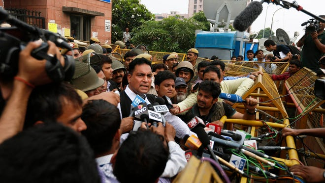 Defense lawyer A.P. Singh, center, speaks to the media after a judge pronounced death sentence for all four men convicted in the rape and murder of a student on a moving New Delhi bus last year, in New Delhi, India, Sept. 13, 2013.