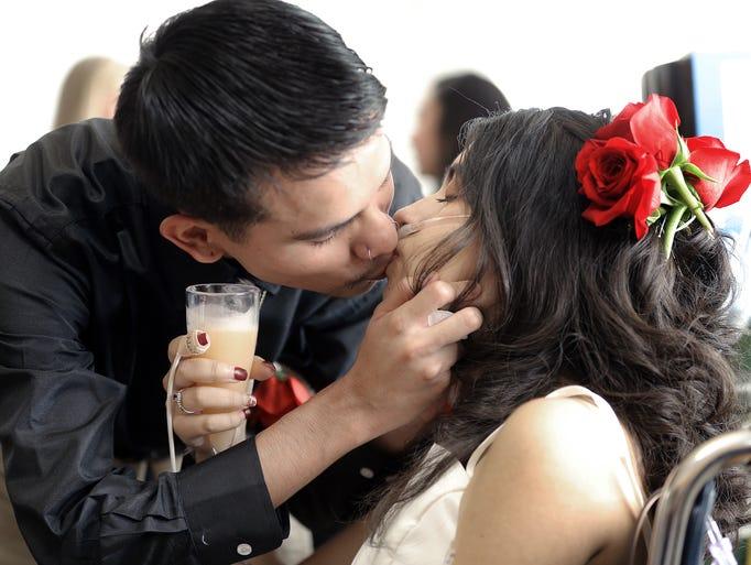 Newlyweds Joshua Ordoñez and Lydia Dominguez kiss following