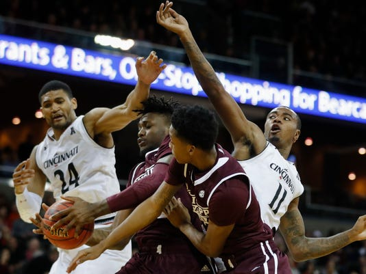 Mississippi State's Schnider Herard (34) rebounds the ball against Cincinnati's Kyle Washington (24) and Gary Clark (11) in the second half of an NCAA college basketball game, Tuesday, Dec. 12, 2017, in Highland Heights, Ohio. Cincinnati won 65-50. (AP Photo/John Minchillo)