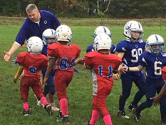 In this Sunday, Oct. 8, 2017 photo, coach John Galligan, left, congratulates players during a Rookie Tackle youth football game in Islip, N.Y. USA Football has introduced the pilot program called Rookie Tackle, a scaled down version of football for young players. (AP Photo/Ralph Russo)