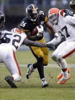 Pittsburgh Steelers running back Le'Veon Bell (26) carries the ball against Cleveland Browns inside linebacker D'Qwell Jackson (52) and outside linebacker Jabaal Sheard (97) during the second quarter at Heinz Field.