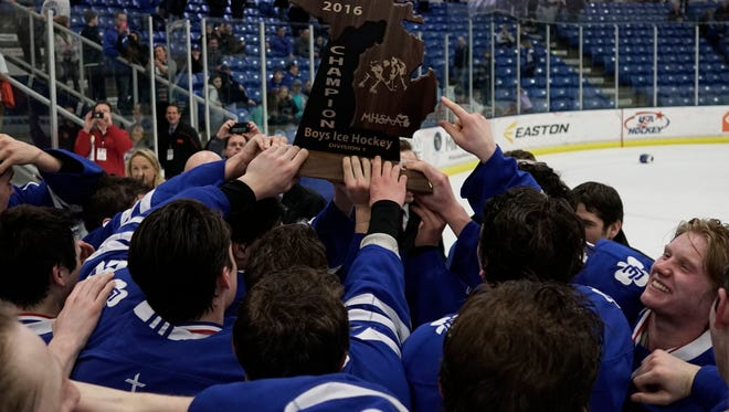 Novi Detroit Catholic Central holds their trophy high after Catholic Central's 3-0 win over Brighton in the Division 1 hockey final Saturday at the USA Hockey Arena in Plymouth.