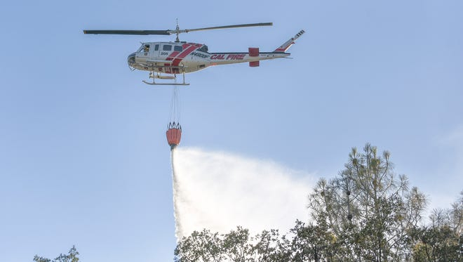 A Cal Fire helicopter drops water on hot spots in Saturday's vegetation fire off Texas Springs Road.