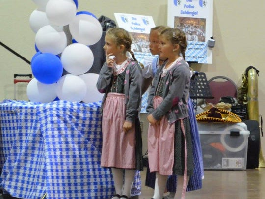 Three little girls dressed in traditional German clothing  look on at the  Ruidoso Oktoberfest.