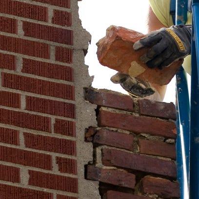 Melissa Staub with Staub Excavating removes a brick