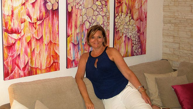Marshfield resident Ines Krolo poses with one of her paintings.