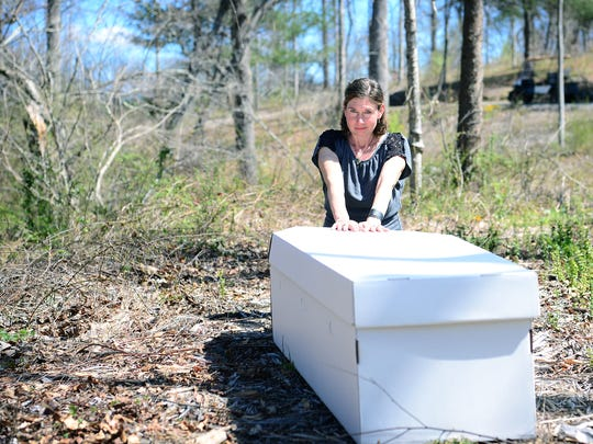 Carol Motley poses with one of the cardboard coffins that her company, Mourning Dove Studios, sells at the green burial cemetery, Carolina Memorial Sanctuary in Mills River on Wednesday, March 29, 2017. The cardboard is purposefully white so family and friends can decorate the burial vessel as they see fit.