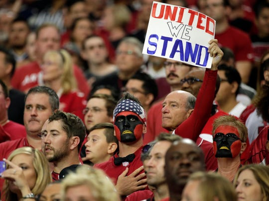 Fans stand during the national anthem prior the football game between the Patriots and the Cardinals, Sunday, Sept. 11, 2016, in Glendale, Ariz.